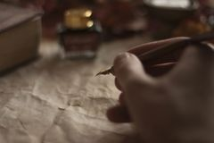Παλαιό έγγραφο με ένα χέρι γραψίματος με το στυλό και το μελάνι φτερών και Βίβλος στον ξύλινο πίνακα στοκ εικόνα με δικαίωμα ελεύθερης χρήσης