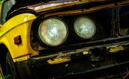 Παλαιό αυτοκίνητο στο εκλεκτής ποιότητας ύφος Το εγκαταλειμμένο σκουριασμένο κίτρινο αυτοκίνητο στους δασικούς προβολείς μπροστιν Στοκ εικόνα με δικαίωμα ελεύθερης χρήσης