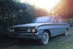 Παλαιό παλαιό αυτοκίνητο ύφους που σταθμεύουν σε έναν κήπο με τους φράκτες γύρω στοκ φωτογραφία