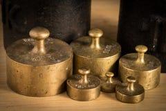 Παλαιό βάρος σιδήρου 1kg και μικρότερα βάρη ορείχαλκου για μια κλίμακα κουζινών Στοκ φωτογραφία με δικαίωμα ελεύθερης χρήσης