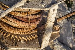 Παλαιό βαρούλκο αποβαθρών σκαφών με τη διαβρωμένη ρόδα εργαλείων και τη σκουριασμένη λεπτομέρεια σπειρών καλωδίων χάλυβα στοκ εικόνα