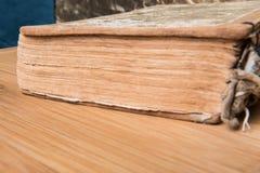Παλαιό βιβλίο ανοικτό σε έναν ξύλινο πίνακα με τα γυαλιά Στοκ Φωτογραφίες