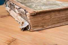 Παλαιό βιβλίο ανοικτό σε έναν ξύλινο πίνακα με τα γυαλιά Στοκ Εικόνες