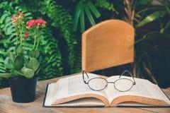 Παλαιό βιβλίο ανοικτό στον πίνακα με τα γυαλιά ανάγνωσης στον κήπο Στοκ Φωτογραφίες