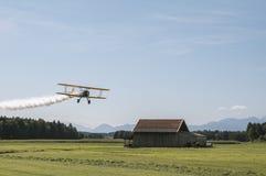 Παλαιό βιο αεροπλάνο που πετά πέρα από το θερινό τοπίο στοκ εικόνες