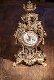 Παλαιό εκλεκτής ποιότητας χρυσό ρολόι χαλκού χαλκού μετάλλων στον ξύλινο πίνακα στοκ εικόνα