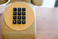Παλαιό κίτρινο τηλέφωνο με το μαύρο βασικό μαξιλάρι Στοκ Φωτογραφίες