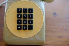 Παλαιό κίτρινο τηλέφωνο με το μαύρο βασικό μαξιλάρι Στοκ εικόνες με δικαίωμα ελεύθερης χρήσης