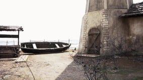 Παλαιό κτήριο με καλά και μια βάρκα footage Παλαιά ξύλινη βάρκα με ένα one-storey σπίτι, καλά και ένας λόφος στα ρωσικά απόθεμα βίντεο