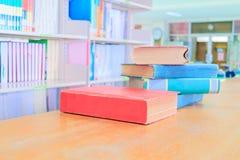 Παλαιό κόκκινο βιβλίων - πράσινο ο σωρός είναι εσωτερικό σχολείο βιβλιοθηκών στον ξύλινο πίνακα και μουτζουρωμένο υπόβαθρο ραφιών στοκ εικόνα