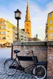 Παλαιό μαύρο ποδήλατο μπροστά από Vor Frelsers Kirke στοκ εικόνα