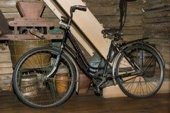 Παλαιό μαύρο σκουριασμένο ποδήλατο στο παλαιό εξοχικό σπίτι Στοκ Εικόνες