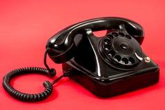 Παλαιό μαύρο τηλέφωνο που απομονώνεται σε ένα κόκκινο υπόβαθρο Στοκ Φωτογραφία