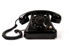 Παλαιό μαύρο τηλέφωνο που απομονώνεται σε ένα κόκκινο υπόβαθρο Στοκ εικόνα με δικαίωμα ελεύθερης χρήσης