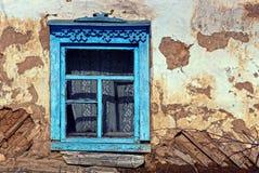 Παλαιό μπλε παράθυρο στον γκρίζο τοίχο ενός αγροτικού σπιτιού Στοκ Φωτογραφία