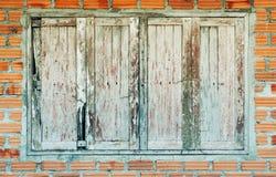 παλαιό ξύλινο παράθυρο με το καφετί υπόβαθρο architechture τούβλων τοίχων Στοκ Εικόνες