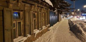 Παλαιό ξύλινο σπίτι ένας-ιστορίας στην οδό το χειμώνα στοκ εικόνα