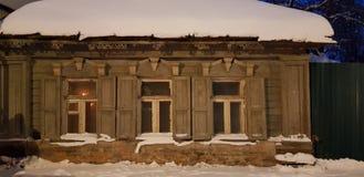 Παλαιό ξύλινο σπίτι ένας-ιστορίας στην οδό το χειμώνα στοκ φωτογραφία