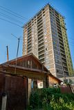 Παλαιό ξύλινο σπίτι μπροστά από έναν μεγάλο ψηλό σύγχρονο ουρανοξύστη στοκ εικόνες με δικαίωμα ελεύθερης χρήσης