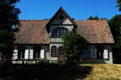 Παλαιό ξύλινο σπίτι που περιβάλλεται από τα δέντρα στοκ φωτογραφίες