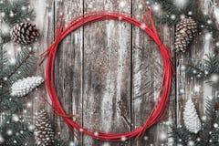 Παλαιό ξύλινο υπόβαθρο, κώνοι έλατου γύρω από έναν κόκκινο κύκλο Διάστημα διακοπών για το χειμώνα, τα Χριστούγεννα, το νέες έτος  Στοκ Φωτογραφία
