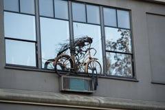 Παλαιό οξυδωμένο ποδήλατο που διακοσμεί το παράθυρο στοκ εικόνες