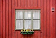 Παλαιό παράθυρο ενός ξύλινου σπιτιού κόκκινου χρώματος, με flowerpot στην πρόσοψη Στοκχόλμη, Σουηδία στοκ φωτογραφία