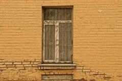 Παλαιό παράθυρο με μια σχάρα σιδήρου σε έναν καφετή τοίχο τούβλου Στοκ εικόνα με δικαίωμα ελεύθερης χρήσης