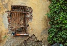 Παλαιό παράθυρο με το πλέγμα μετάλλων σε έναν παλαιό εγκαταλειμμένο αποφλοίωση τοίχο με στοκ εικόνες
