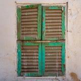 Παλαιό παράθυρο grunge με τα κλειστά πράσινα παραθυρόφυλλα στο βρώμικο τοίχο πετρών τούβλων στοκ εικόνες με δικαίωμα ελεύθερης χρήσης