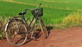 Παλαιό ποδήλατο και πορτοκαλί καλάθι στο δρόμο χώματος και λάσπης στην επαρχία το πρωί μετά από να βρέξει χθες βράδυ Στοκ Εικόνες