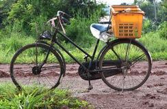 Παλαιό ποδήλατο και πορτοκαλί καλάθι στο δρόμο χώματος και λάσπης στην επαρχία το πρωί μετά από να βρέξει χθες βράδυ Στοκ εικόνα με δικαίωμα ελεύθερης χρήσης