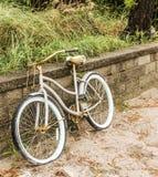 Παλαιό ποδήλατο παραλιών με ένα επίπεδο ενάντια σε έναν τοίχο πετρών στην άμμο Στοκ Φωτογραφία