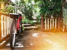 Παλαιό ποδήλατο στο ξύλινο πάτωμα εκλεκτής ποιότητας υπόβαθρο σπιτιών και φύσης Στοκ Εικόνα