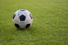 Παλαιό ποδόσφαιρο σφαιρών στο νέο πράσινο χλόη-έδαφος Στοκ Εικόνες
