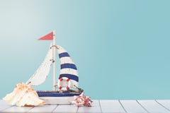 Παλαιό πρότυπο παιχνιδιών βαρκών πανιών με τη ρόδα, το σχοινί και το θαλασσινό κοχύλι σκαφών ` στο άσπρο και μπλε ξύλινο υπόβαθρο Στοκ Εικόνες