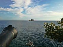 Παλαιό πυροβόλο, μικρό νησί, ουρανός και θάλασσα Στοκ Εικόνες