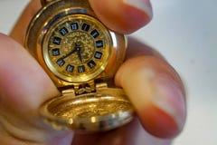 Παλαιό παλαιό ρολόι τσεπών σε μια αλυσίδα υπό εξέταση στοκ φωτογραφίες