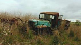 Παλαιό σκουριασμένο εγκαταλειμμένο αυτοκίνητο στον τομέα απόθεμα βίντεο