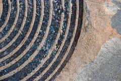Παλαιό σκουριασμένο κυκλικό σχέδιο κάλυψης καταπακτών με την άμμο ή ρύπος στην άκρη Στοκ Εικόνες