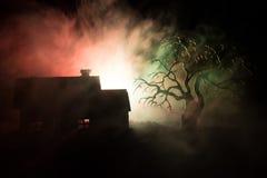 Παλαιό σπίτι με ένα φάντασμα τη νύχτα με το απόκοσμο δέντρο ή εγκαταλειμμένο συχνασμένο σπίτι φρίκης στον τονισμένο ομιχλώδη ουρα Στοκ φωτογραφίες με δικαίωμα ελεύθερης χρήσης