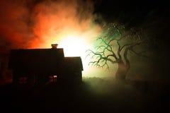 Παλαιό σπίτι με ένα φάντασμα τη νύχτα με το απόκοσμο δέντρο ή εγκαταλειμμένο συχνασμένο σπίτι φρίκης στον τονισμένο ομιχλώδη ουρα Στοκ Εικόνες