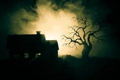 Παλαιό σπίτι με ένα φάντασμα τη νύχτα με το απόκοσμο δέντρο ή εγκαταλειμμένο συχνασμένο σπίτι φρίκης στον τονισμένο ομιχλώδη ουρα Στοκ εικόνες με δικαίωμα ελεύθερης χρήσης