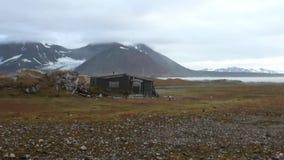 Παλαιό σπίτι στην ακτή ερήμων του αρκτικού ωκεανού στο υπόβαθρο των βουνών φιλμ μικρού μήκους
