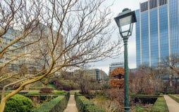 Παλαιό φανάρι οδών και πράσινη περιοχή πάρκων γύρω από το θερμοκήπιο πορτοκαλιών και τους αστικούς πύργους οικοδόμησης πόλεων στοκ φωτογραφία με δικαίωμα ελεύθερης χρήσης
