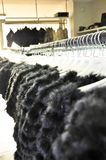 Παλτά γουνών πολυτέλειας που κρεμούν στο ράφι στοκ εικόνες