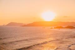 Παλτά και ωκεανός με τα κύματα στο θερμή ηλιοβασίλεμα ή την ανατολή στοκ φωτογραφίες