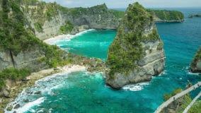 Πανέμορφη άποψη στα κυλώντας κύματα, στους απότομους βράχους και την αμμώδη παραλία στο κατώτατο σημείο με το σαφές διαφανές ωκεά φιλμ μικρού μήκους