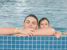 πανέμορφη άποψη του εφήβου και του μικρού κοριτσιού που παίζουν και που χαλαρώνουν στην υπαίθρια πισίνα Στοκ εικόνα με δικαίωμα ελεύθερης χρήσης