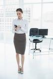 Πανέμορφη ήρεμη επιχειρηματίας που στέκεται στο γραφείο της που χρησιμοποιεί το smartphone της Στοκ Φωτογραφία
